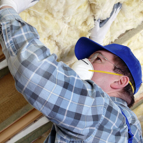 A Technician Installs Insulation in an Attic.