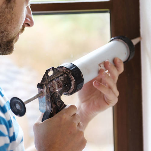 A Man Caulks a Window to Prevent Energy Loss.
