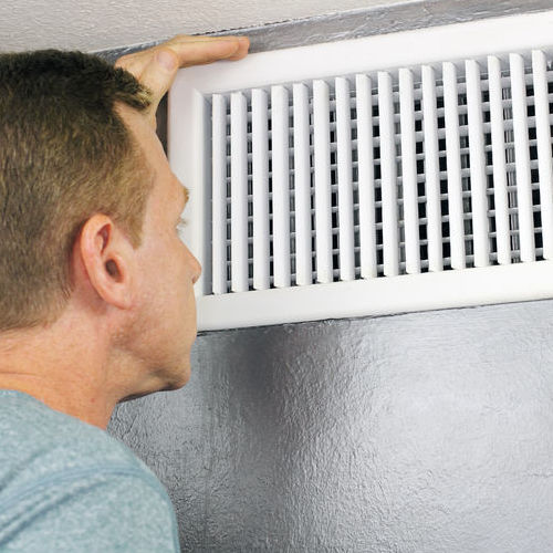 A Technician Checks an Air Vent.