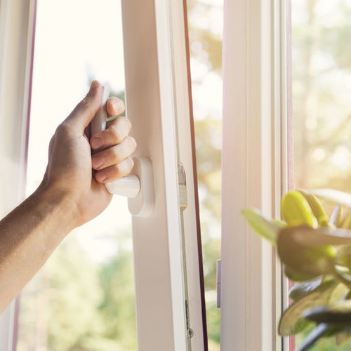 A Woman Opens a Window to Check Ventilation.