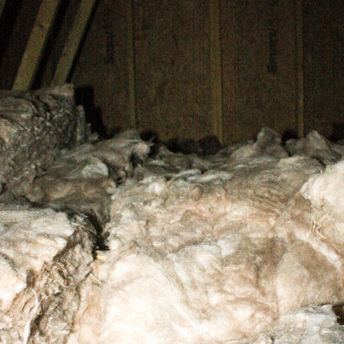An Attic With Dirty Insulation.